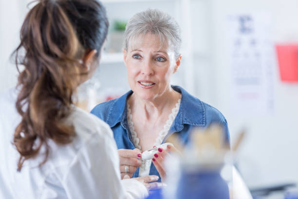 serious senior woman talks with doctor - diabetes stock pictures, royalty-free photos & images