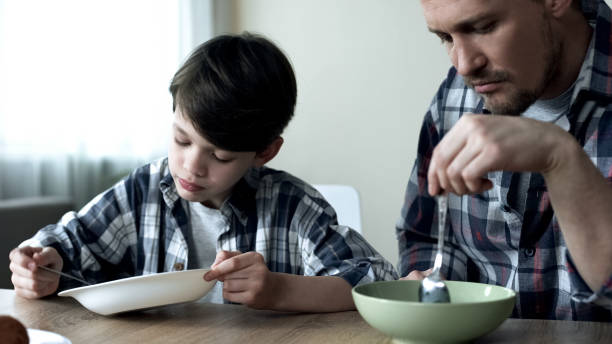 Serious single father and his son eating cornflakes in morning, poor breakfast Serious single father and his son eating cornflakes in morning, poor breakfast hungry child stock pictures, royalty-free photos & images