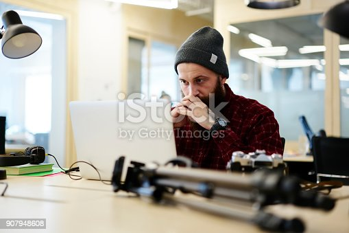 Serious skilled photographer dressed in trendy outfit carefully watching video on laptop connected to wireless internet.Young concentrated employee working on modern, device sitting in workspace