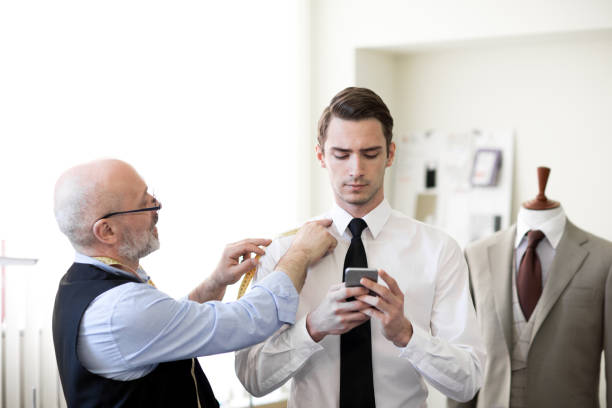 Serious skilled senior tailor in glasses measuring shoulder of customer while he texting message in smartphone in sewing studio stock photo