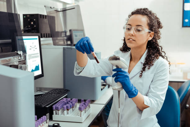 Serious smart female researcher studying human DNA stock photo