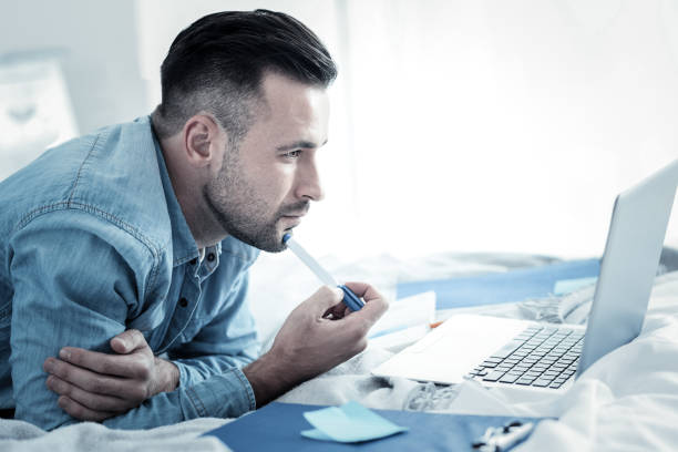 Serious smart man holding a pen stock photo