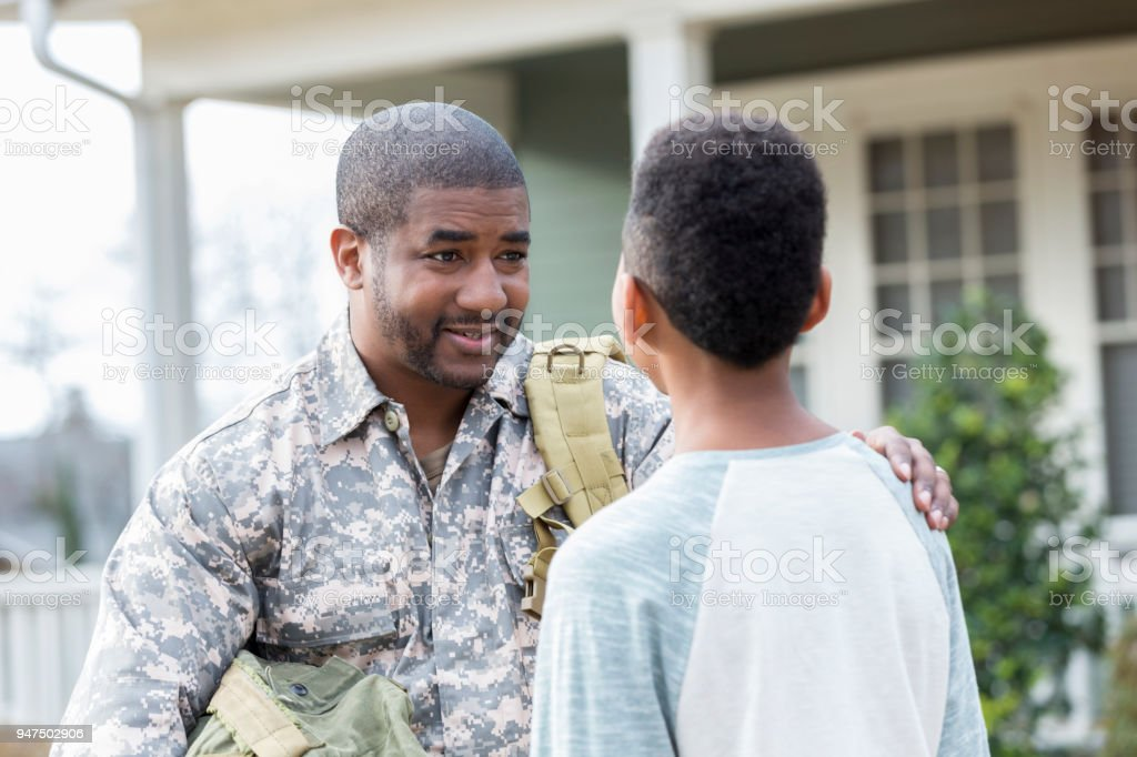 Serious soldier gives son advice stock photo
