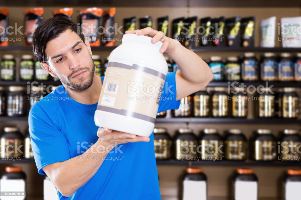 Serious sportman choosing different sport nutrition products stock photo