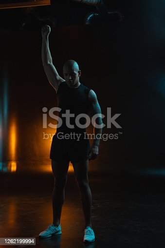 Thoughtful professional athlete in sports clothes putting one fist up while standing against the dark background with orange light on it