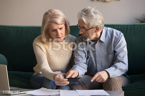 istock Serious stressed old couple looking at calculator feeling worried 1173667031