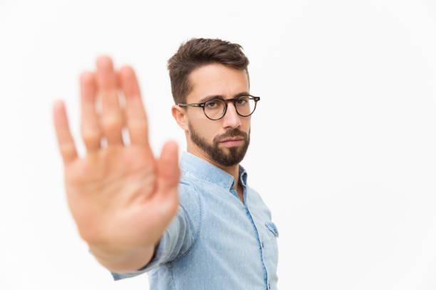 Seriöser strenger Kerl macht Hand-Stopp-Geste – Foto