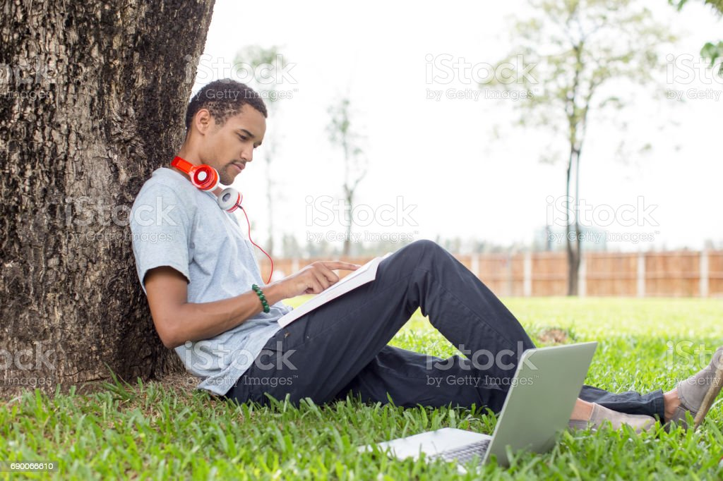Serious student man reading textbook in campus stock photo