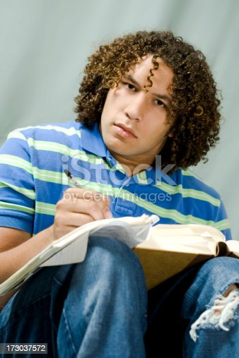 Student sits down and takes notes from his literature book.
