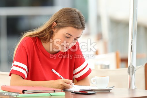 820495452 istock photo Serious student studying taking notes in a bar 849181366