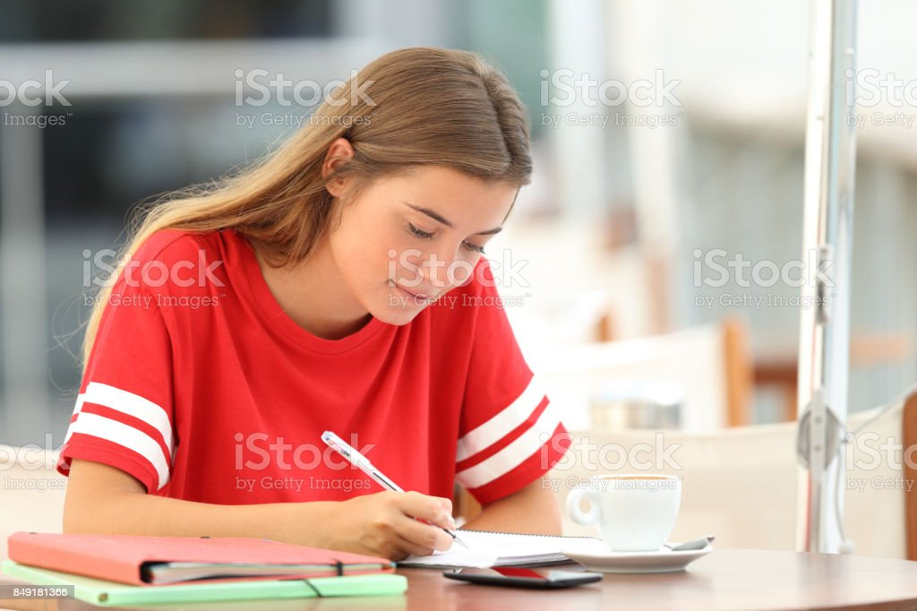 Serious student studying taking notes in a bar stock photo