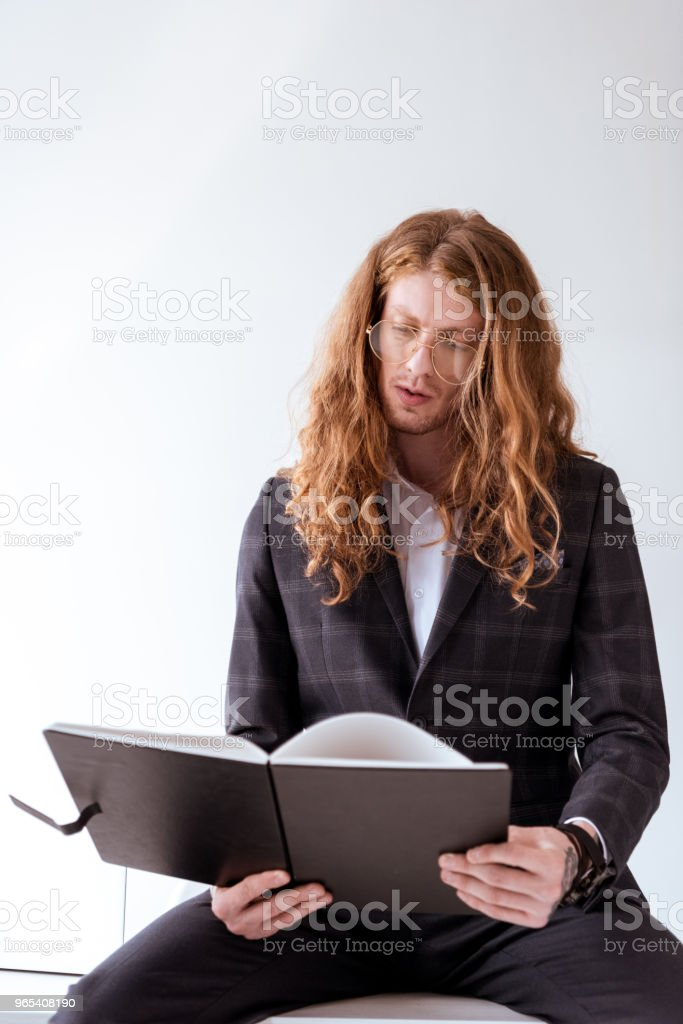 serious stylish tattooed businessman with curly hair sitting on table and reading documents royalty-free stock photo