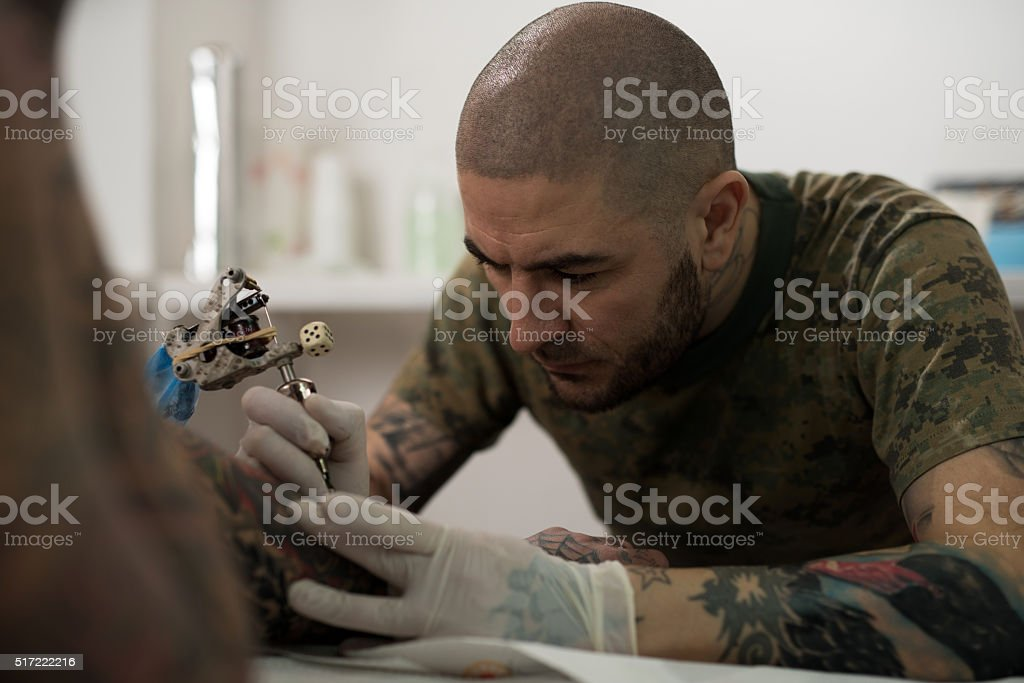 Serious Tattoo Artist Drawing Tattoo On Customers Arm Stock
