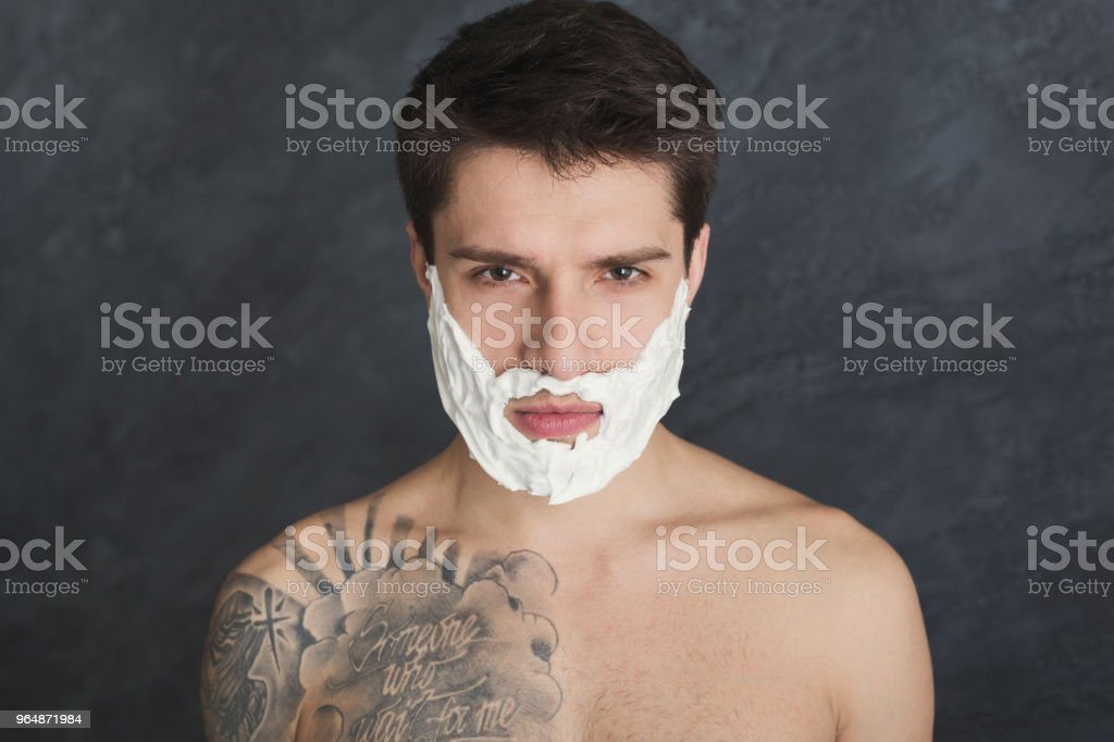 Serious tattooed man with foam on face royalty-free stock photo
