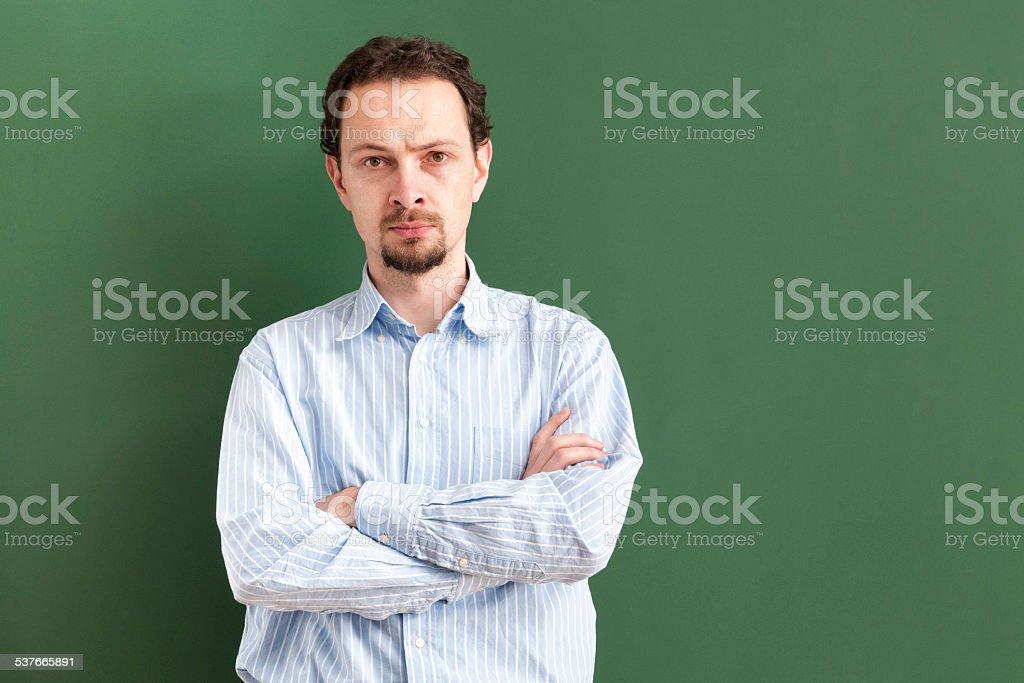 Graves professor de pé com os braços cruzados com Quadro Negro - fotografia de stock
