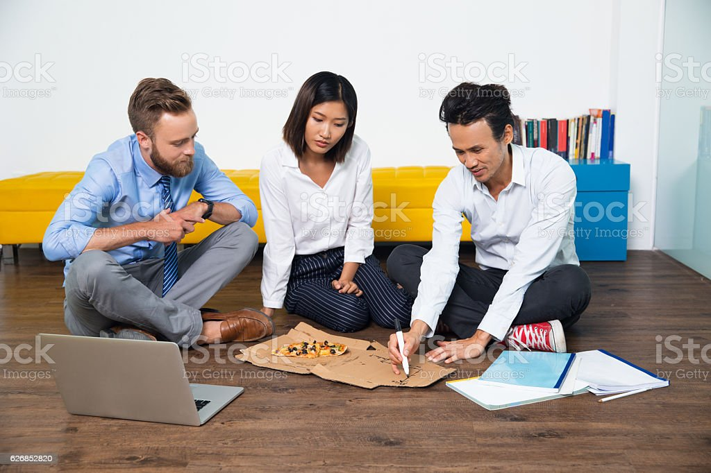 Serious team discussing strategy on pizza box stock photo