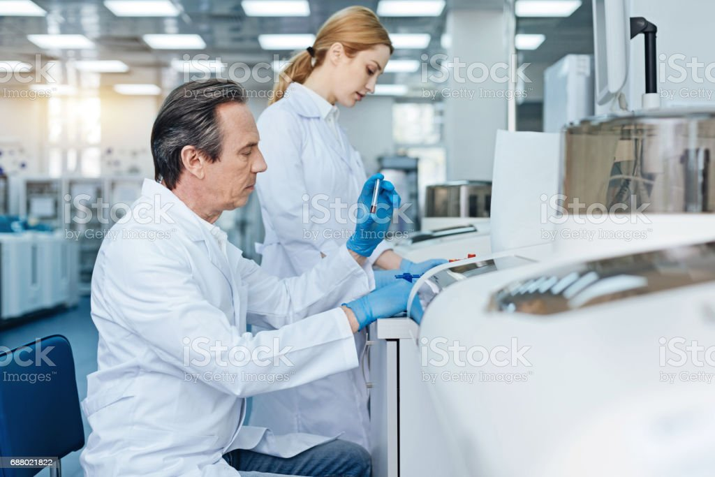 Serious technician doing blood analysis stock photo