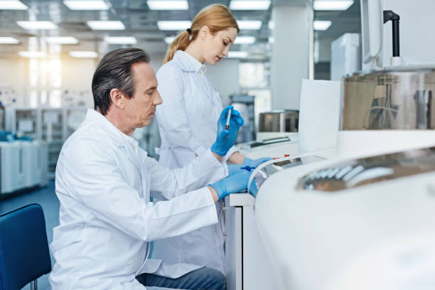 Serious technician doing blood analysis Seriousness at work. Gray-haired male person sitting in semi position and raising left hand while looking at test-tube dna purification stock pictures, royalty-free photos & images