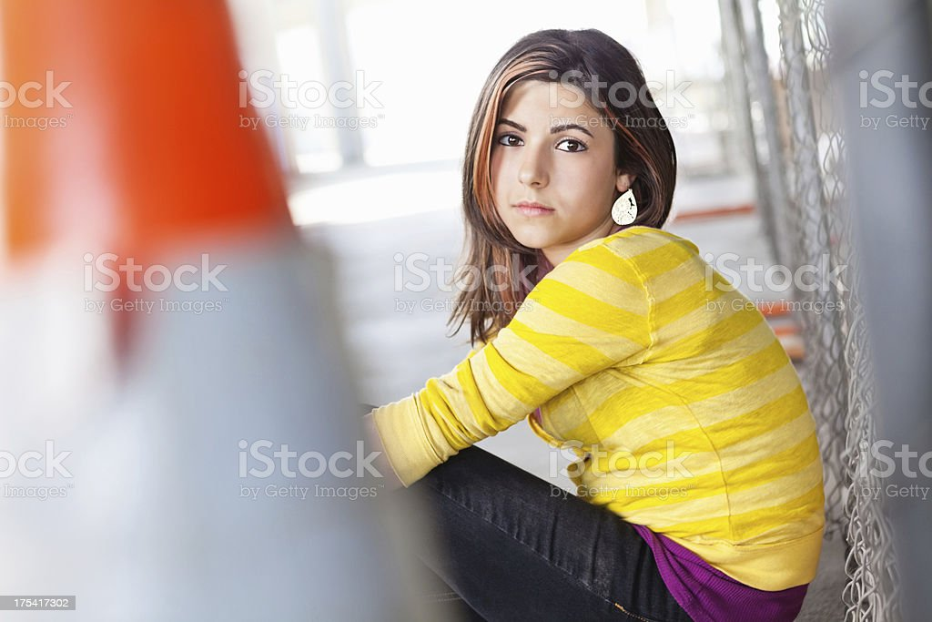 Serious teen girl sitting by fence royalty-free stock photo