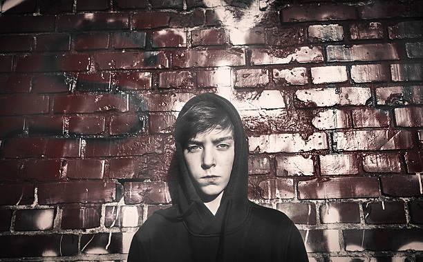 schwere teenager-jungen vor einem roten graffiti - schlechte laune sprüche stock-fotos und bilder