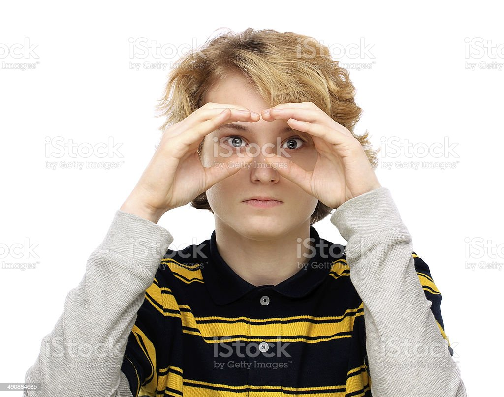 Serious teenage boy   shielding eyes and looking.White background stock photo