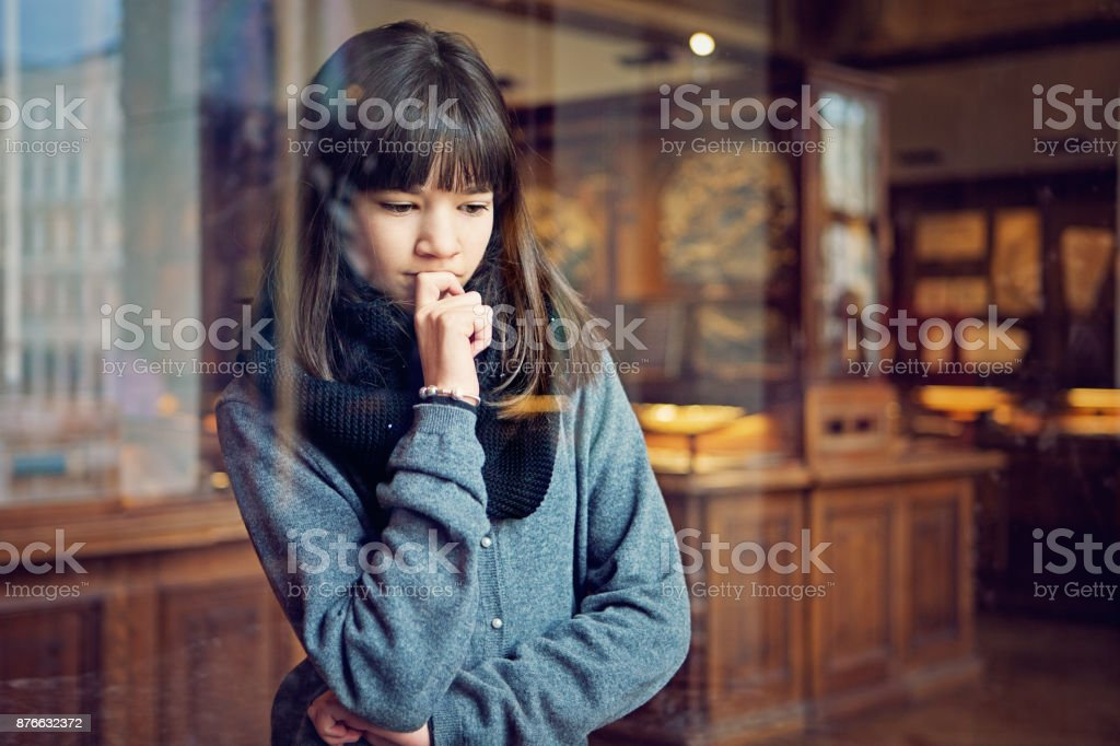 Serious teenage girl is looking museum exhibition with interest stock photo