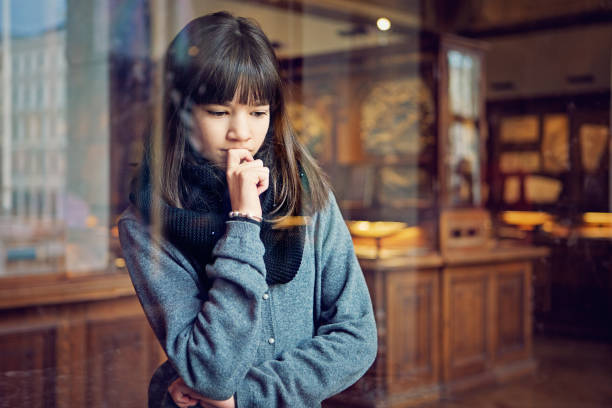 serious teenage girl is looking museum exhibition with interest - museu imagens e fotografias de stock