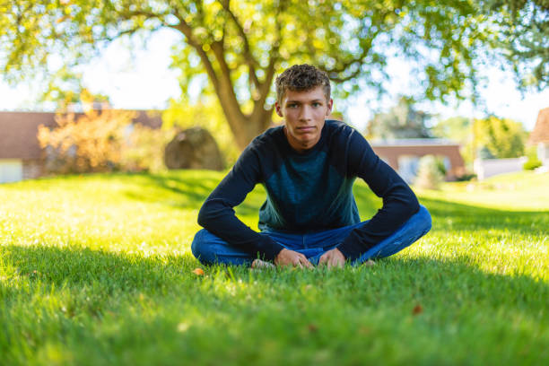 Serious Teenage Male of Mixed Racial Ethnicity Sitting on Grassy Area in Shade Afro-Latinx lifestyle in the US Photo Series In Western Colorado Teenage Male of Mixed Racial Ethnicity Sitting on Grassy Area in Shade Afro-Latinx lifestyle in the US Photo Series (Shot with Canon 5DS 50.6mp photos professionally retouched - Lightroom / Photoshop - original size 5792 x 8688 downsampled as needed for clarity and select focus used for dramatic effect) eyecrave stock pictures, royalty-free photos & images