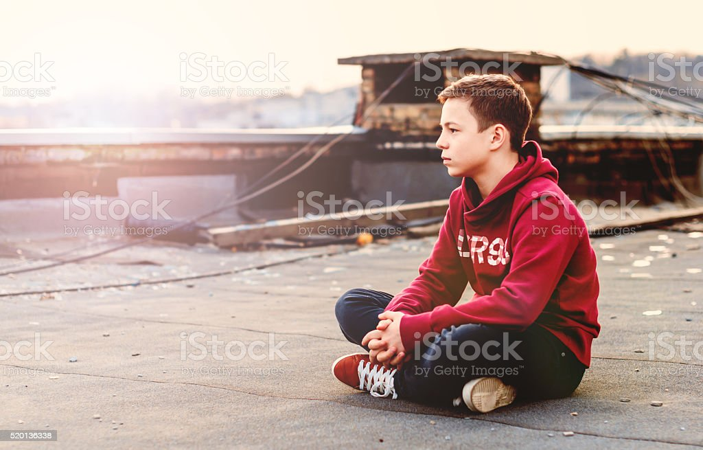 serious teenager sitting on the roof of the house stock photo