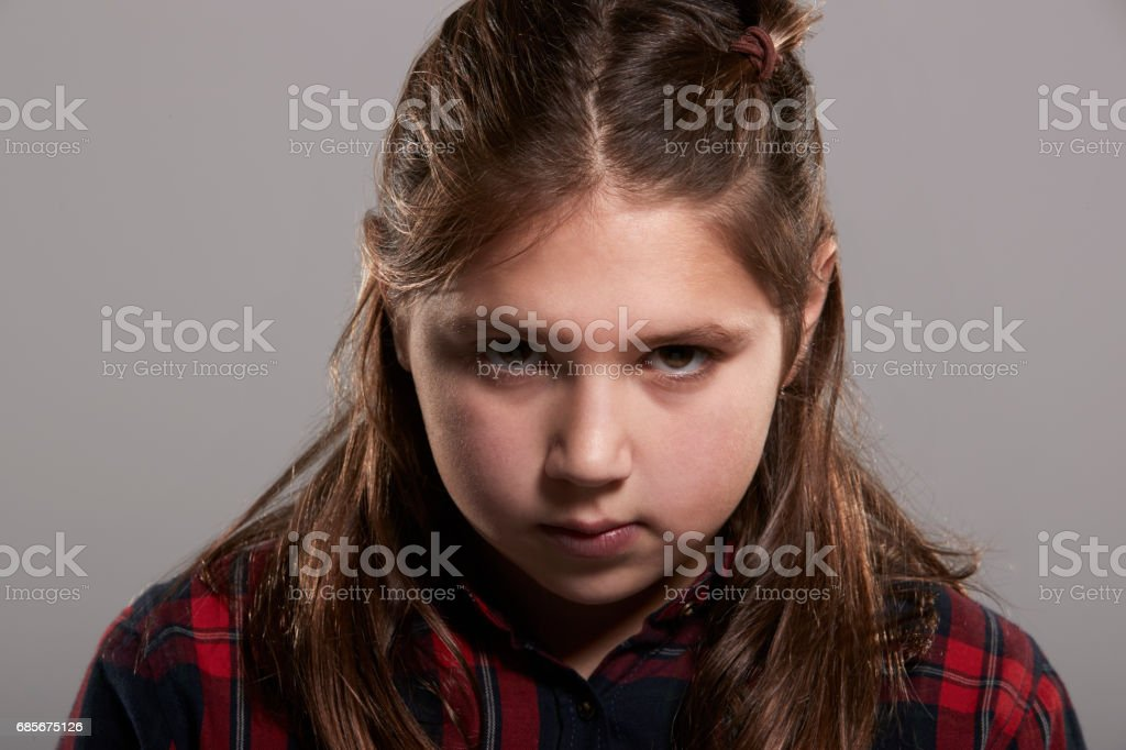 Garota de dez ano de idade séria olhando para a câmera, cabeça e ombros - foto de acervo