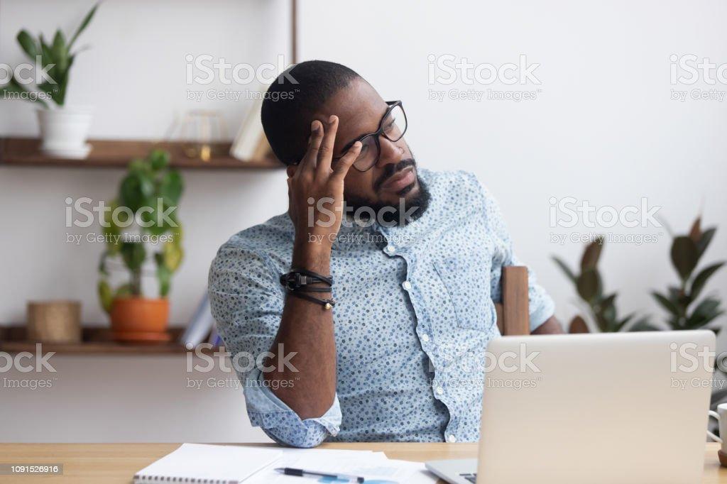 机に座って深刻な思慮深いアフリカの実業家 - 1人のロイヤリティフリーストックフォト