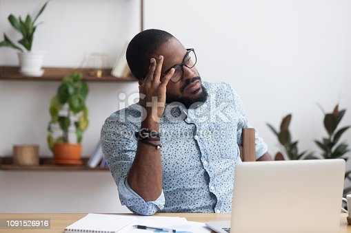 istock Serious thoughtful african businessman sitting at desk 1091526916