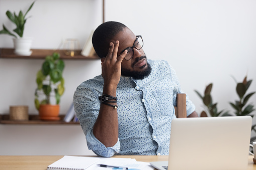 Serious Thoughtful African Businessman Sitting At Desk Stock Photo - Download Image Now