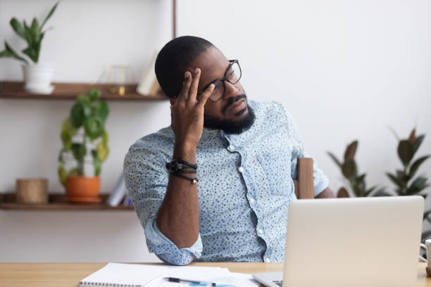 Serious thoughtful african businessman sitting at desk Serious african millennial businessman thinking cogitating about business issues. Frustrated black entrepreneur searching problem solution sitting alone on chair at modern office desk looking away ambiguity stock pictures, royalty-free photos & images