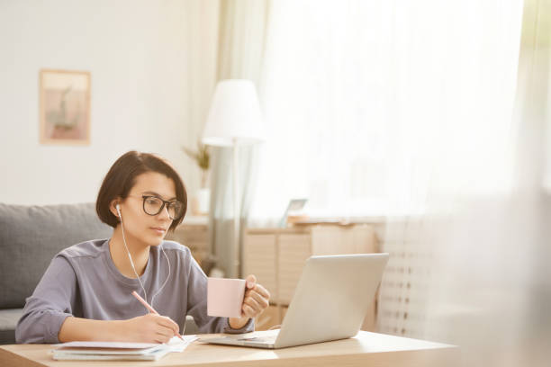 Serious thoughtful young freelance specialist in glasses sitting at coffee table in cozy apartment and drinking coffee while transcribing audio to text stock photo