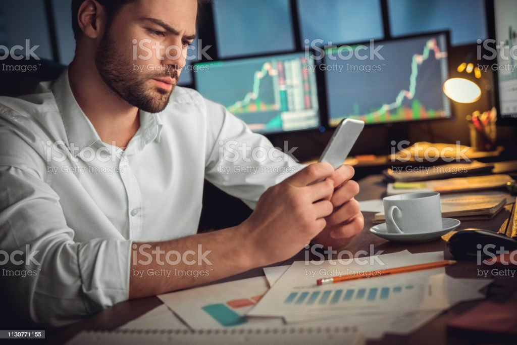 Serious trader using mobile app on smartphone for data analysis Serious trader using mobile phone app on smartphone for checking stock trading data analysis concept, focused businessman holding cellphone working in office with financial graph on computer monitors Adult Stock Photo