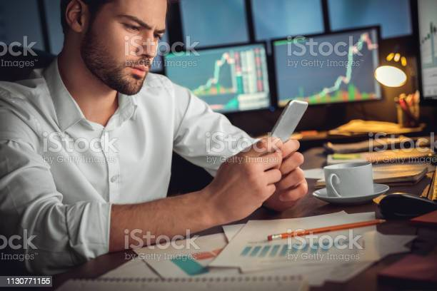 Serious Trader Using Mobile App On Smartphone For Data Analysis Stock Photo - Download Image Now