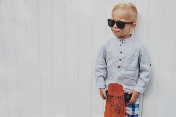 ernst trendige kleiner junge mit seinem skateboard posieren. - sonnenbrille kleinkind stock-fotos und bilder