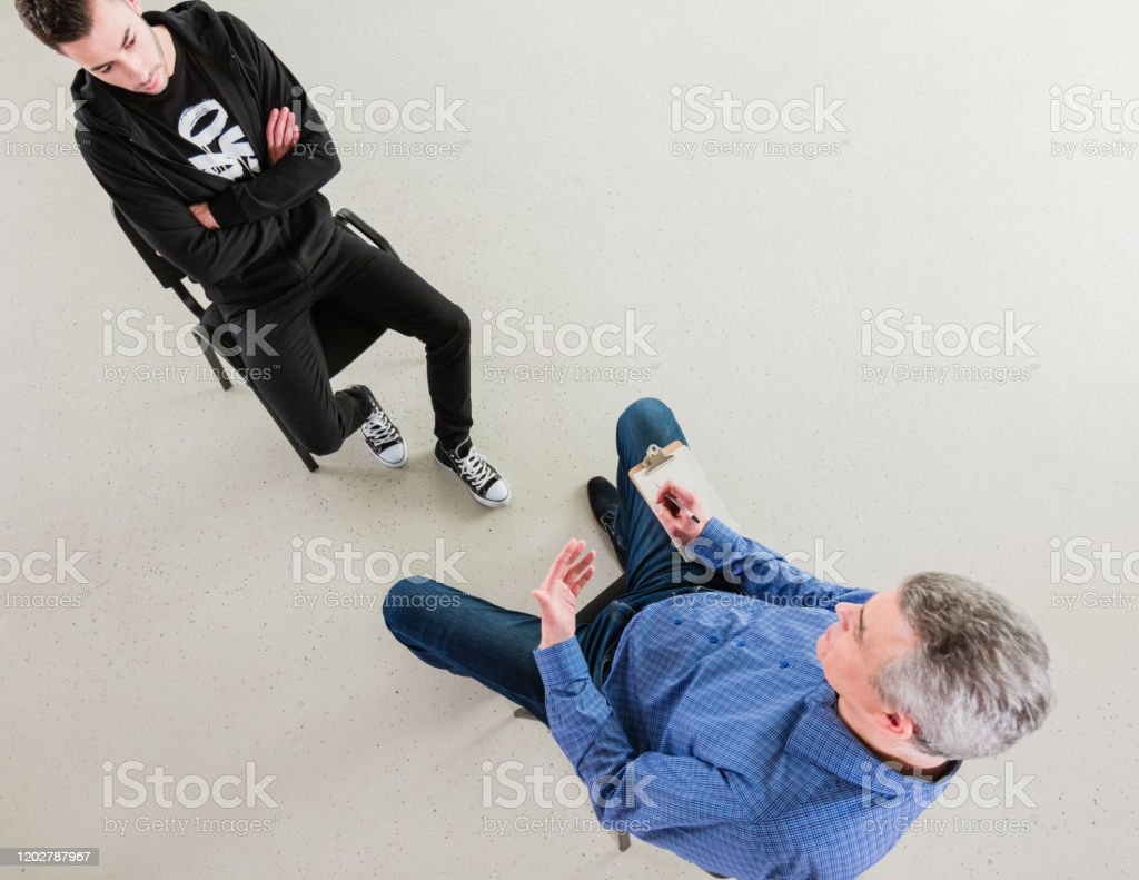 Serious university student listening to therapist High angle view of serious student listening to therapist. Mature professional is advising young man during session. They are sitting in meeting at lecture hall. 18-19 Years Stock Photo
