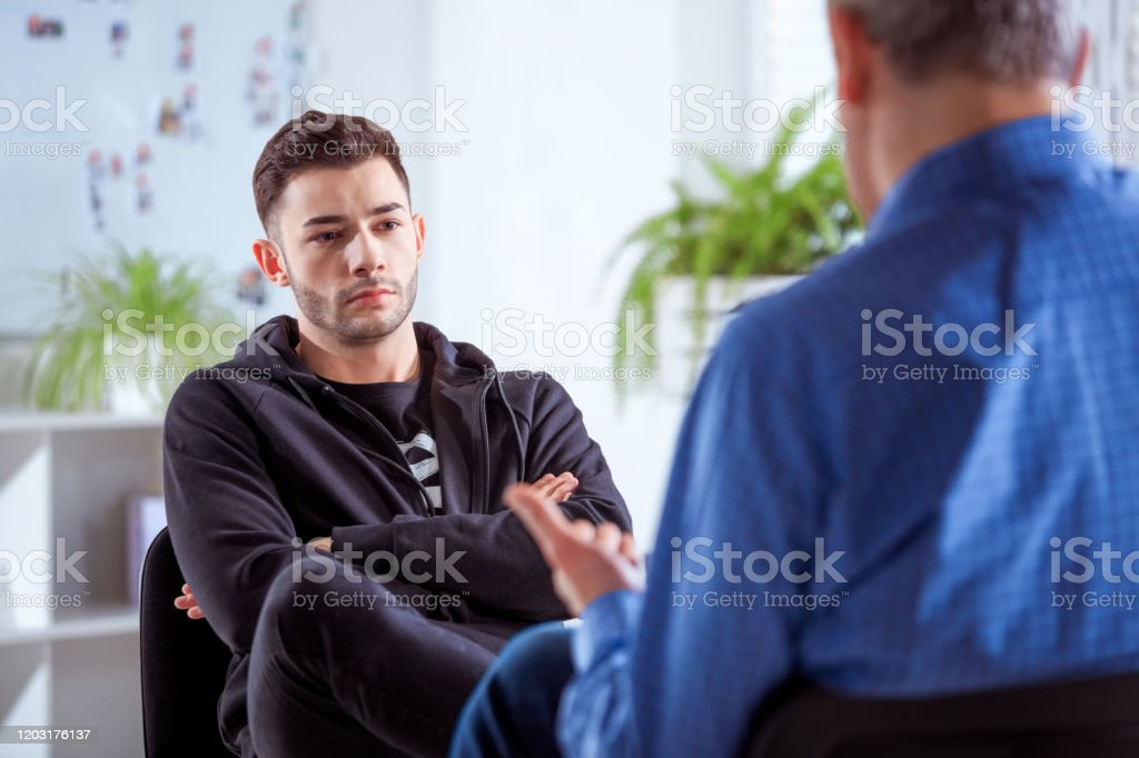 Serious university student listening to therapist Serious student listening to therapist. Mature professional advising young man during session. They are sitting in meeting at lecture hall. 18-19 Years Stock Photo