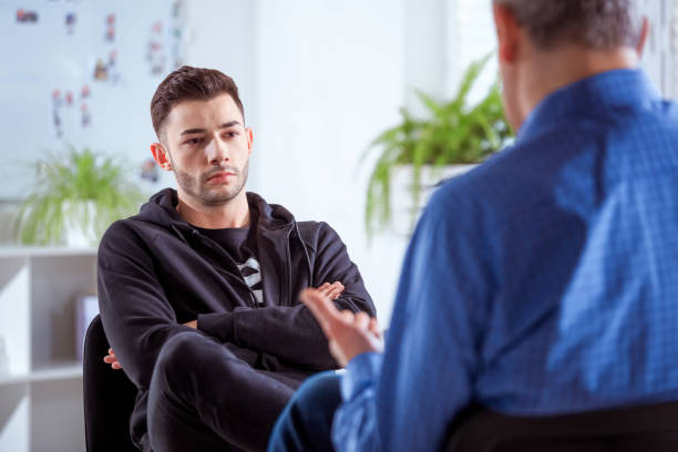 Serious university student listening to therapist stock photo