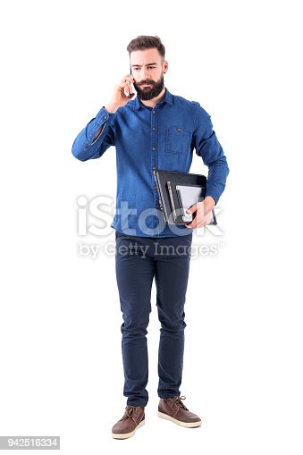 istock Serious upset professional business man talking on the phone carrying laptop and tablet under arm looking down 942516334