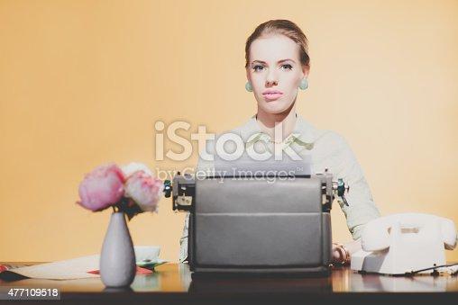 istock Serious vintage 1950 blonde secretary woman sitting behind desk 477109518