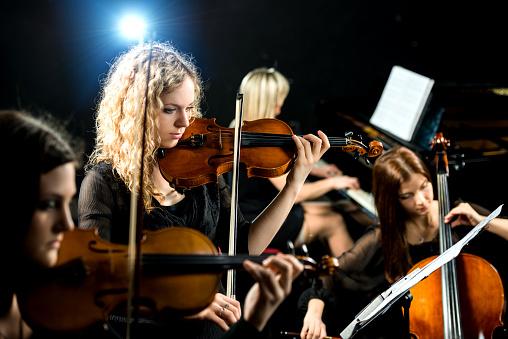 Serious violinist in female quartet.