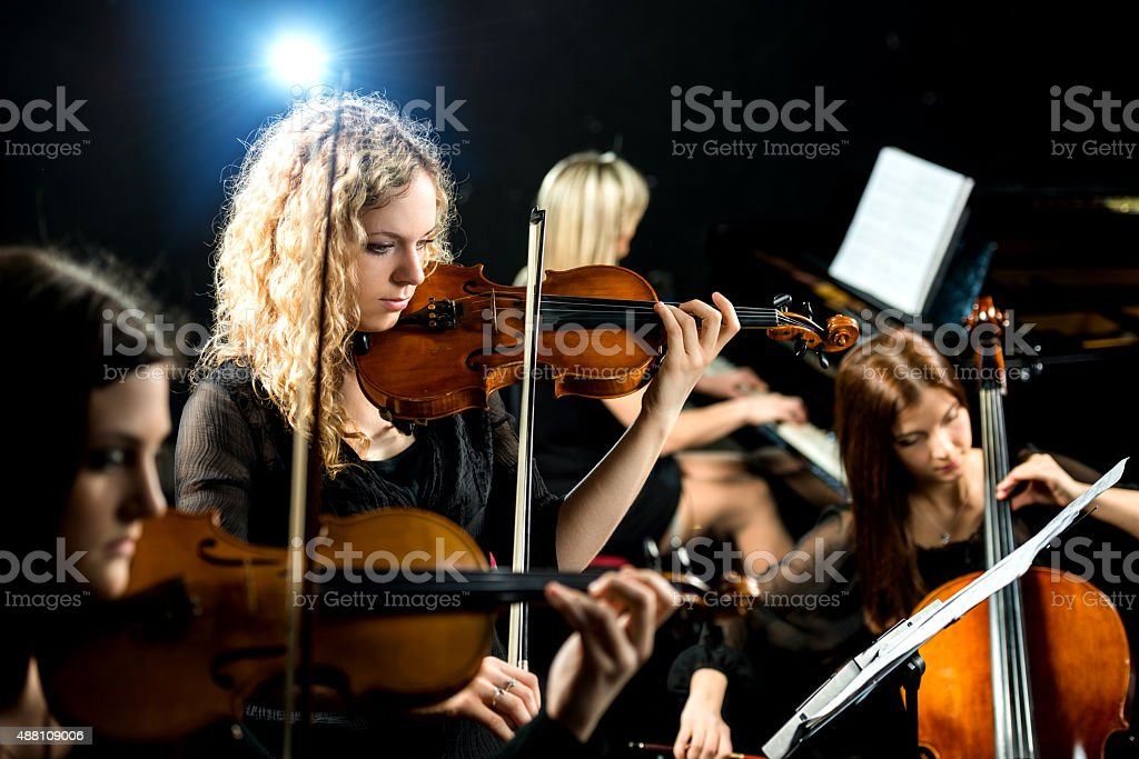 Serious violinist in female quartet. stock photo
