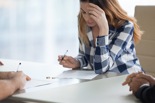 istock Serious wife signing divorce decree in lawyer office 1051395300