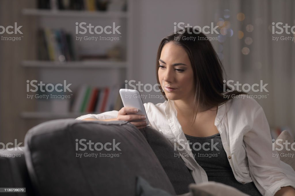 Serious woman checking smartphone content in the night - Royalty-free A usar um telefone Foto de stock