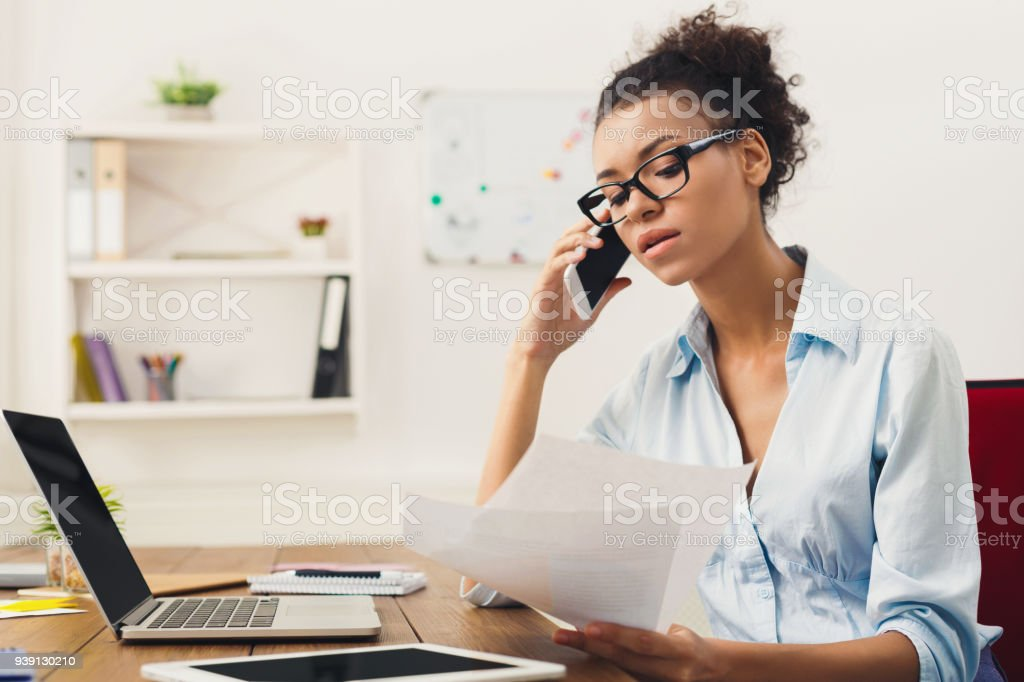 Serious woman consulting by phone at office stock photo
