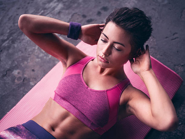 serious woman doing sit ups on a pink exercise mat - sit ups stock photos and pictures