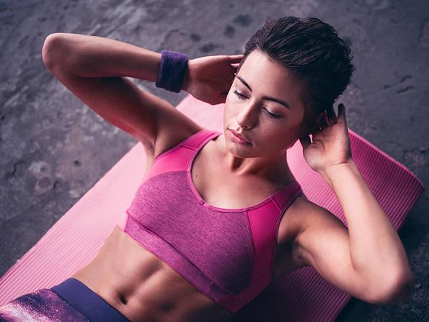 ernst frau macht sit-ups auf einer rosa gymnastikmatte - rosa training stock-fotos und bilder